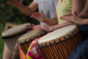 Group,Of,People,Playing,At,Djembe,Drums,Outdoor