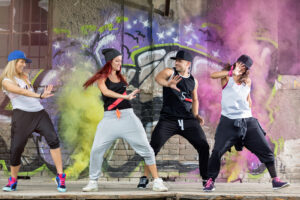Young,Modern,Dancing,Group,Practice,Dancing,In,Front,Colorful,Wall